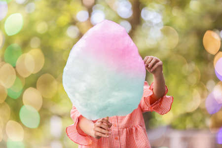 Woman with colorful cotton candy outdoors
