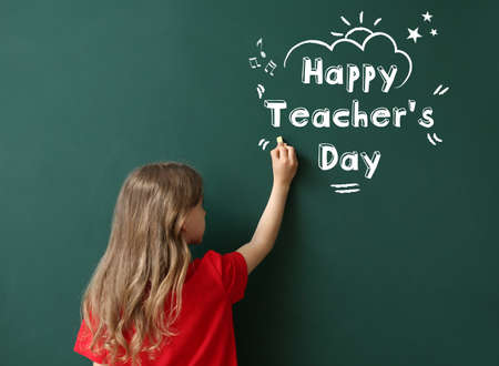 Cute little schoolgirl writing text HAPPY TEACHER'S DAY on blackboard in classroom Standard-Bild