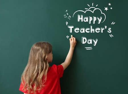 Cute little schoolgirl writing text HAPPY TEACHER'S DAY on blackboard in classroom Фото со стока