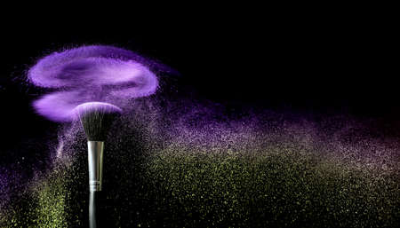 Makeup brush and burst of cosmetics on dark background
