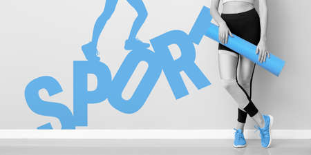 Young woman with yoga mat near light wall with word SPORT