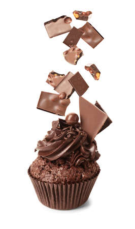 Tasty cupcake and falling sweet chocolate on white background