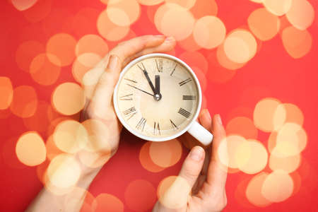Female hands with cup and clock on color background with blurred lights