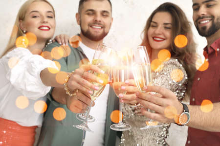 Young people clinking glasses of tasty champagne at party