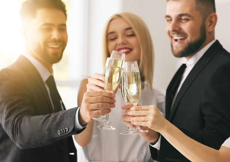 Young people clinking glasses of tasty champagne at party in office