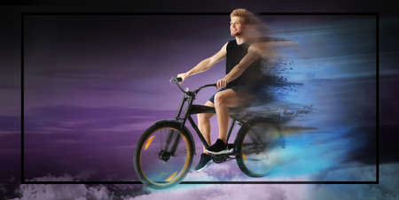 Sporty young man riding bicycle on dark color background