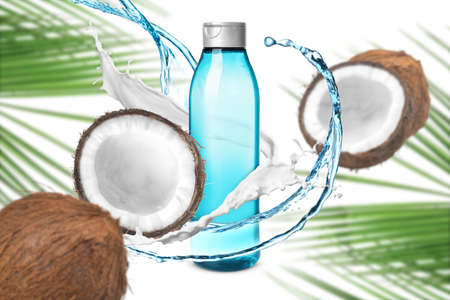 Composition with bottle of shampoo, splashes and coconuts on white background