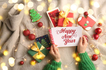 Woman with New Year greeting card and gifts at home, top view