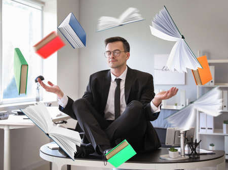 Flying books and meditating businessman in office. Zen concept