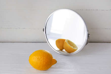 Lemon looking at its reflection in mirror on white wooden background