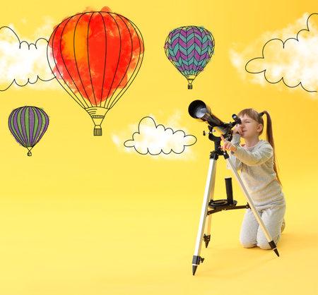 Little girl observing hot air balloons through a telescope in sky Stock fotó