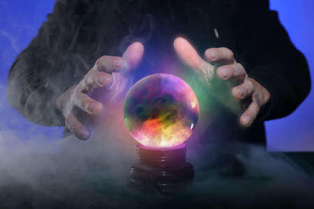 Fortune teller with crystal ball on color background, closeup Standard-Bild