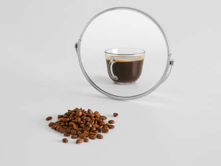 Coffee beans looking at its reflection in mirror on light background Archivio Fotografico