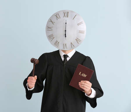 Male judge with clock instead of head on light background. Time management concept