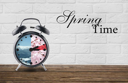 Alarm clock on table against white brick background with text SPRING TIME. Concept of time change Foto de archivo
