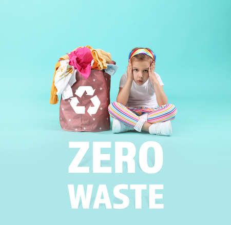 Concerned little girl with clothes in basket on color background. Zero waste concept