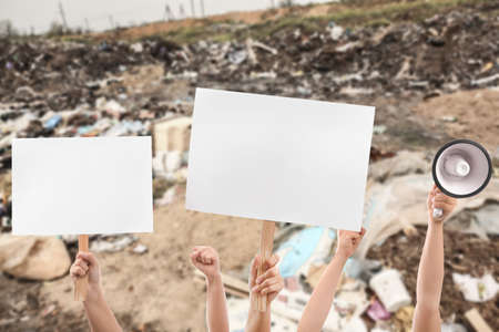 Hands of protesting people with megaphone and placards on landfill site