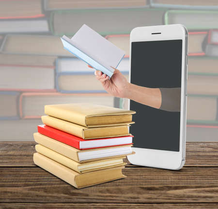 Stack of books and mobile phone on table. Concept of online library