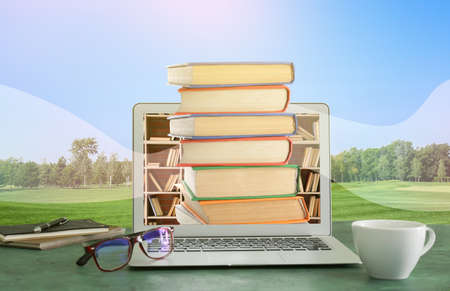 Modern laptop with books on table in park. Concept of online library Imagens