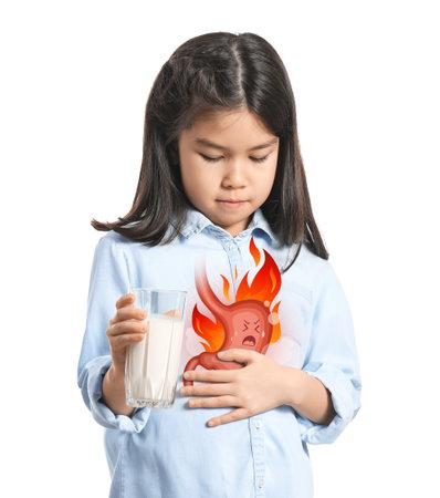 Little Asian girl drinking milk to relieve heartburn on white background