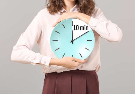 Businesswoman holding clock with timer for 10 minutes on gray background. Time management concept