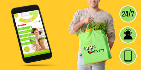 Young man holding bag with food from supermarket and mobile phone with open page of delivery service on color background Stock fotó