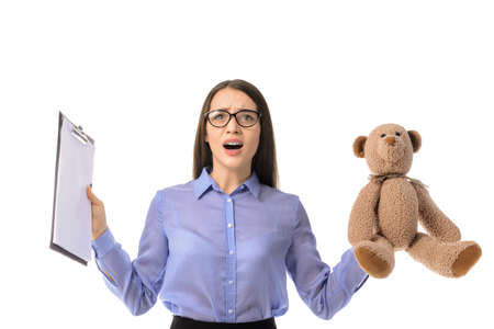 Troubled young businesswoman with toy and clipboard on white background