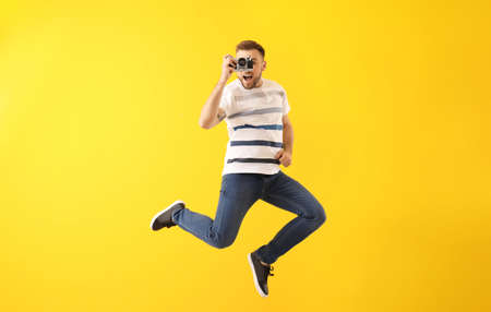 Jumping young man with photo camera on color background