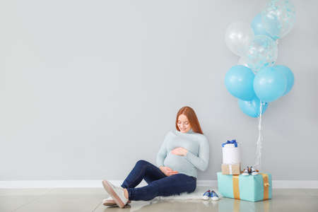 Beautiful pregnant woman with baby shower gifts near light wall Imagens