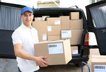 Handsome delivery man near car with parcels outdoors Stock Photo