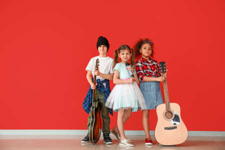Band of little musicians against color wall