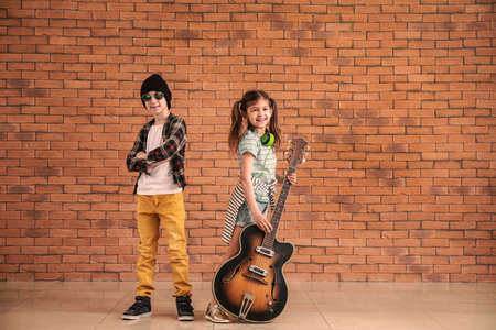 Band of little musicians against brick wall