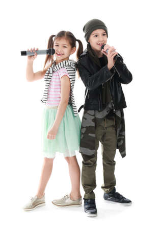 Cute little singers with microphones on white background