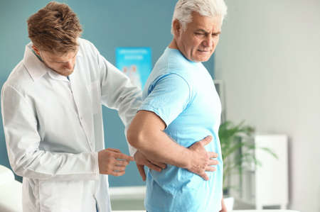Urologist examining male patient in clinic Stock Photo