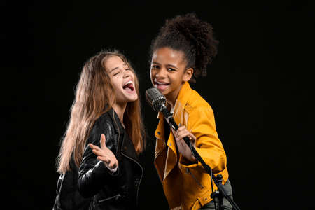 Teenage girls with microphone singing against dark background