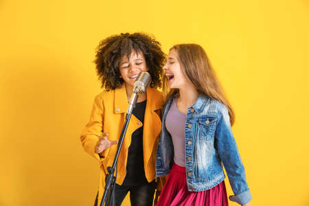 Teenage girls with microphone singing against color background