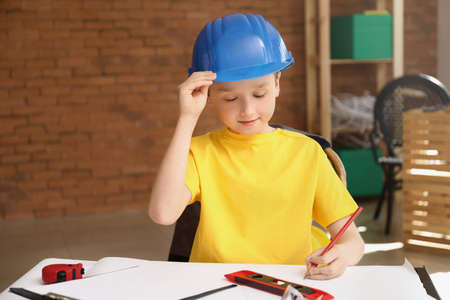 Cute little architect at table indoors