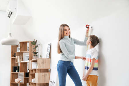 Mother measuring height of her son near wall