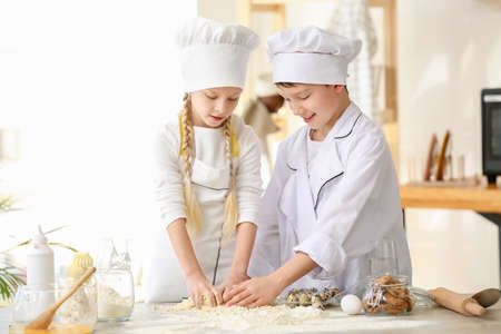 Cute little chefs cooking in kitchen