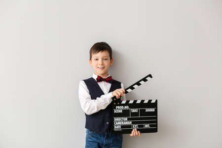 Little boy with clapperboard on white background