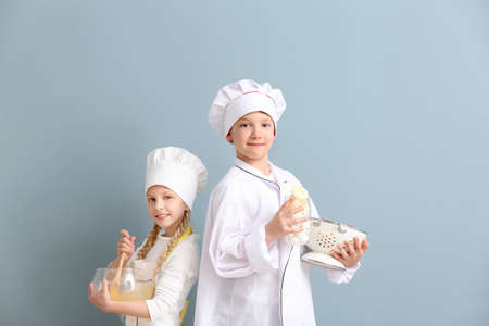 Cute little chefs on color background