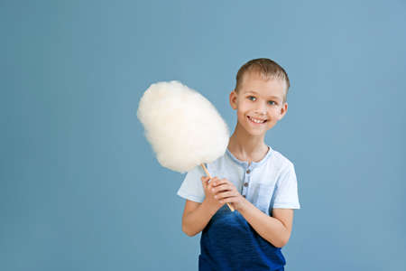 Cute little boy with cotton candy on color background Zdjęcie Seryjne