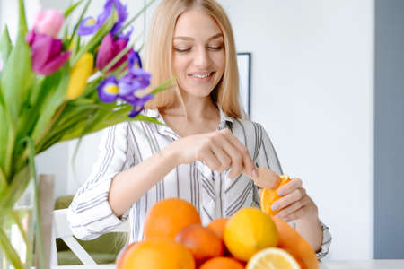 Beautiful young woman squeezing juice from orange at home