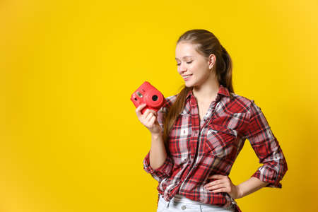 Young female photographer on color background