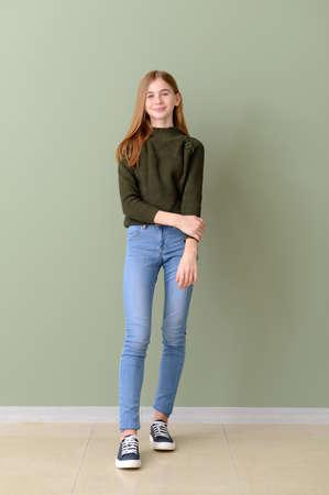 Cute teenage girl near color wall