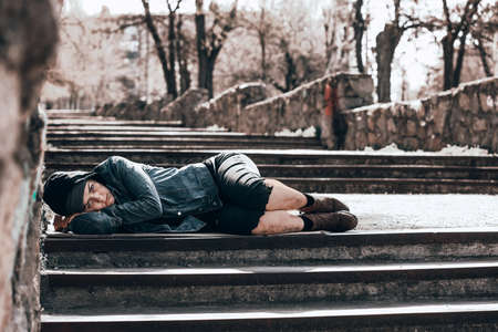 Poor homeless woman lying on stairs outdoors