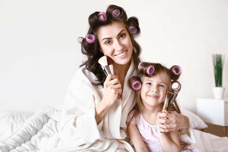 Mother with cute daughter doing makeup at home