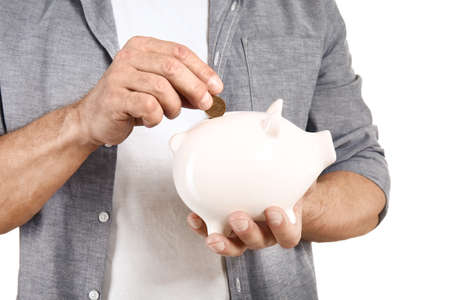Handsome middle-aged man putting coin into piggy bank on white background