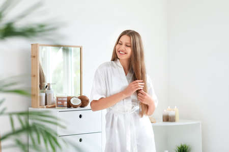 Beautiful young woman applying coconut oil on hair at home