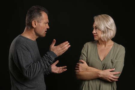 Quarrelling middle-aged couple on dark background